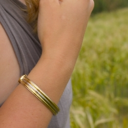lady wearing a polished gold with silver trim duet bracelet