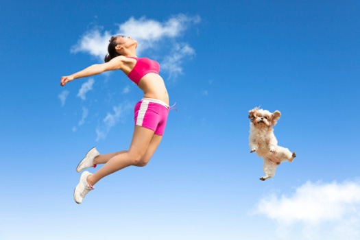 healthy girl and dog both jumping for joy